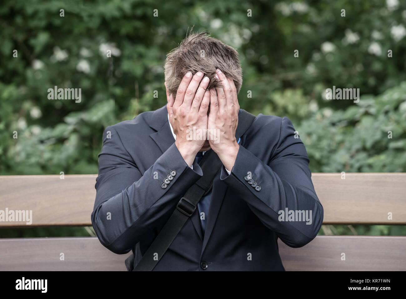 Sad Businessman Sitting On Bench - Stock Image