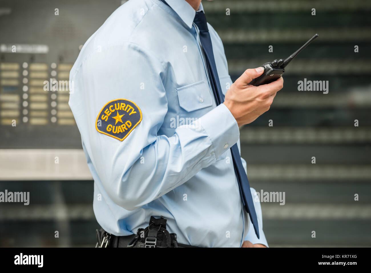 Security Guard Using Walkie-talkie - Stock Image