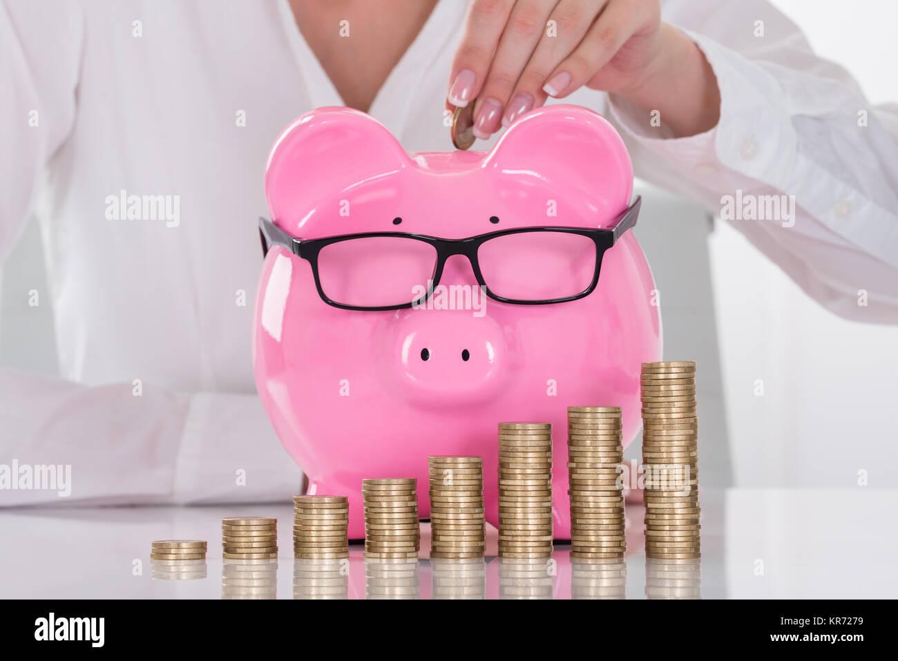Female's Hand Inserting Coin In Piggybank Stock Photo