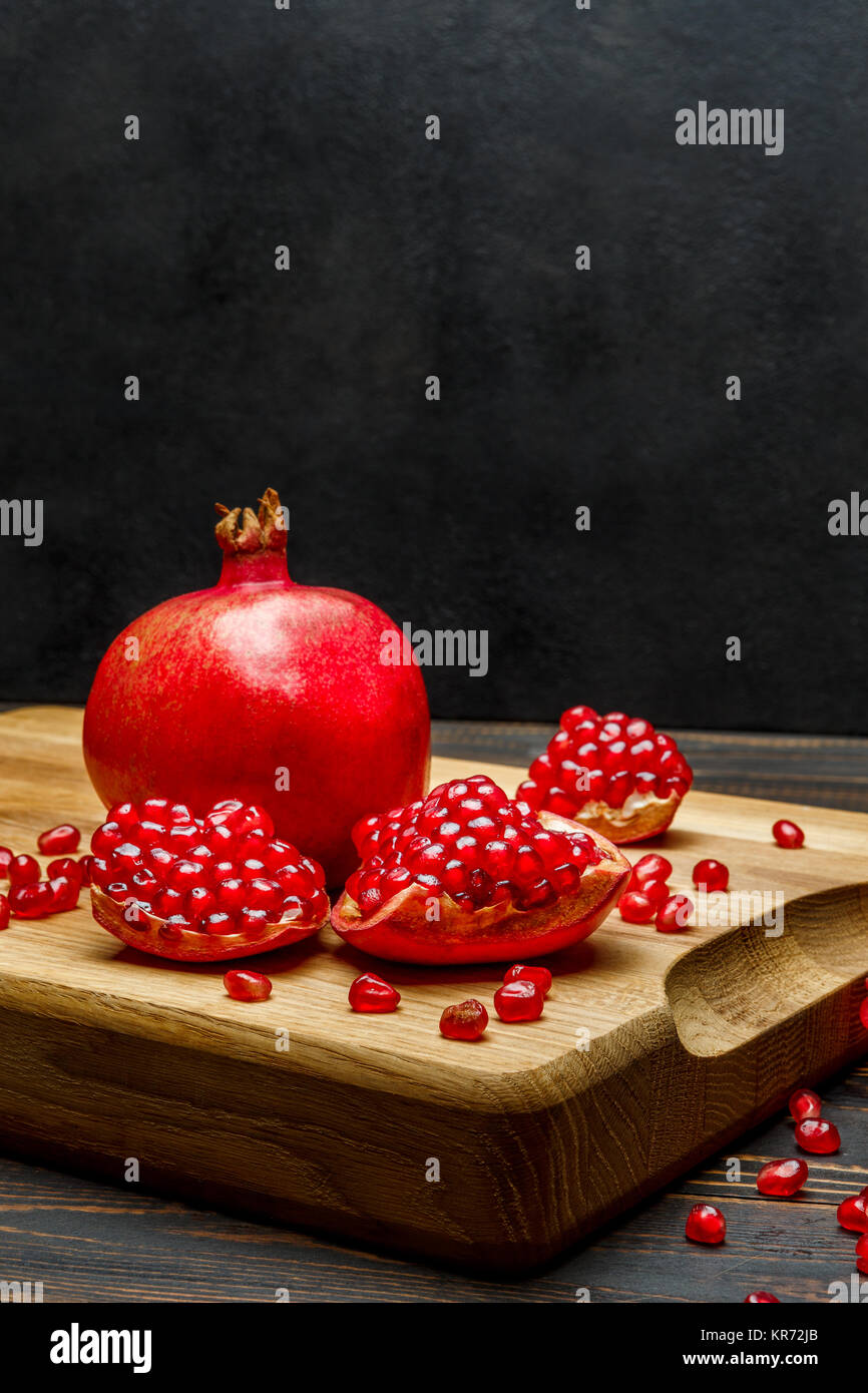 Pomegranate and seeds close-up on wooden background Stock Photo