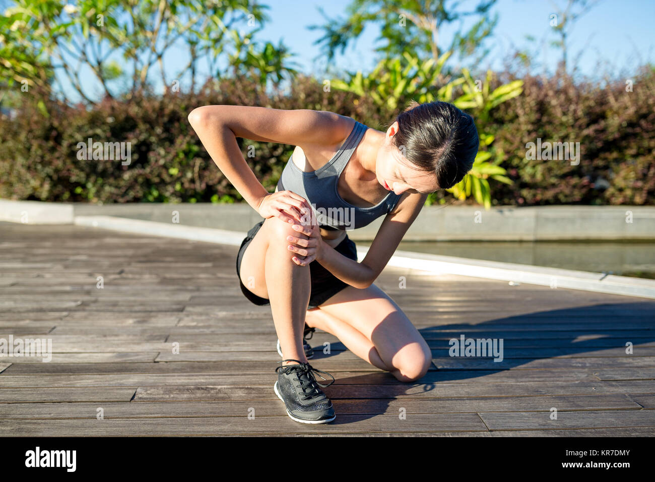 Woman runner hold her sports injured knee - Stock Image