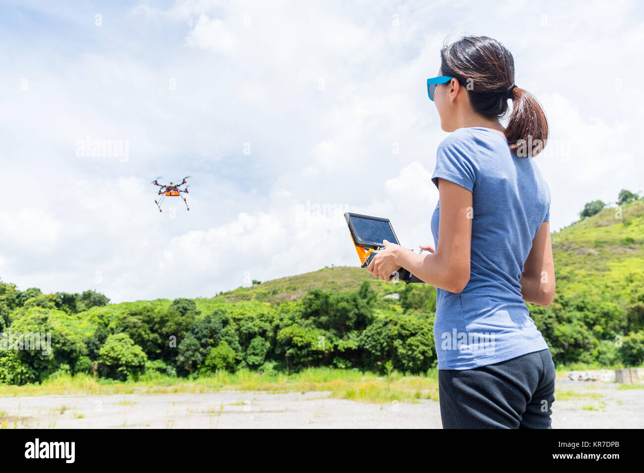 Young Woman remote flying drone - Stock Image