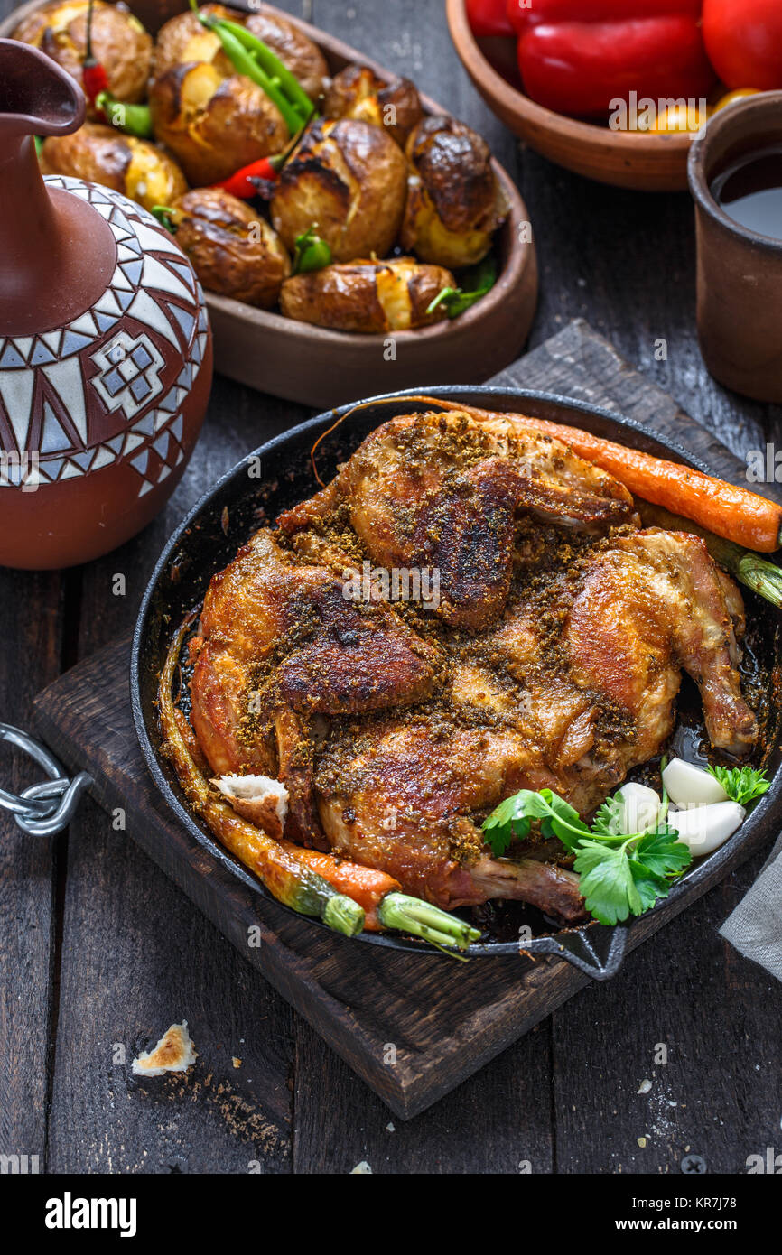 Whole roast chicken in an iron pan on dark background - Stock Image