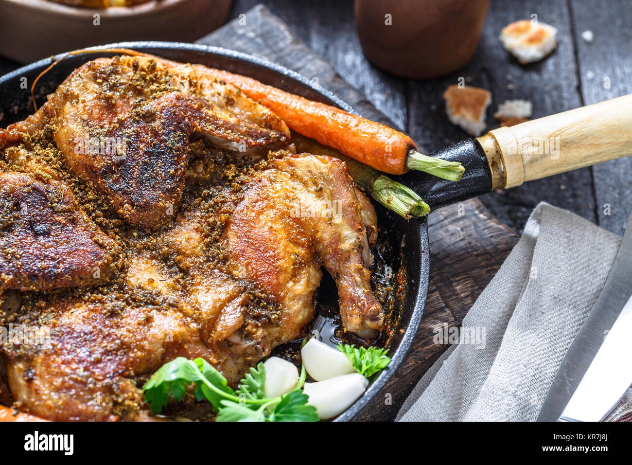 Whole roast chicken in an iron pan, rustic style, close view - Stock Image