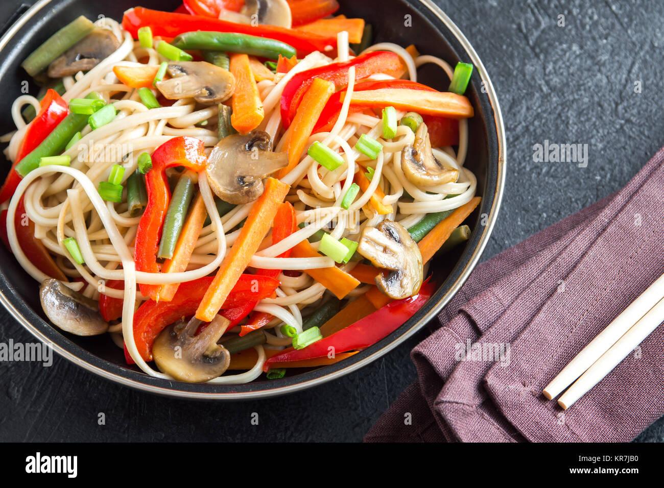 Stir fry with udon noodles, mushrooms and vegetables. Asian vegan vegetarian food, meal, stir fry over black background, - Stock Image