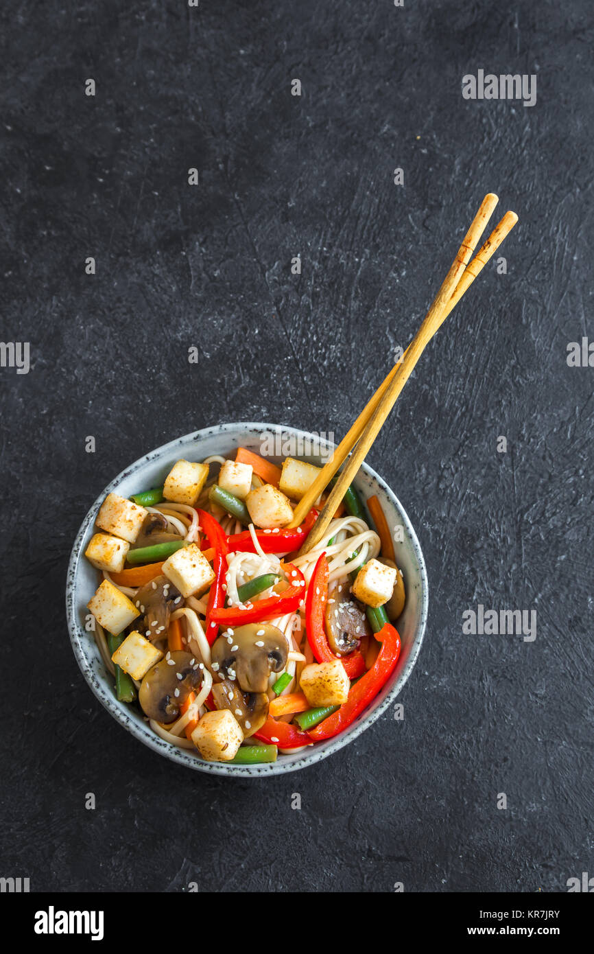 Stir fry with udon noodles, tofu, mushrooms and vegetables. Asian vegan vegetarian food, meal, stir fry over black Stock Photo