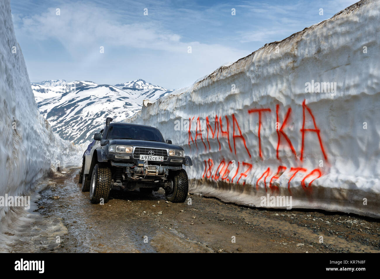 Kamchatka Peninsula: Japanese off-road expedition car Toyota Land Cruiser driving on mountain road in snow tunnel - Stock Image