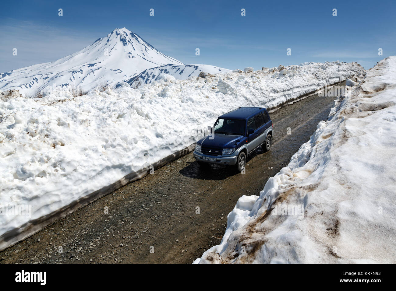 Kamchatka Peninsula, Russia: Japanese off-road car Mitsubishi driving on mountain road in snow tunnel on background - Stock Image
