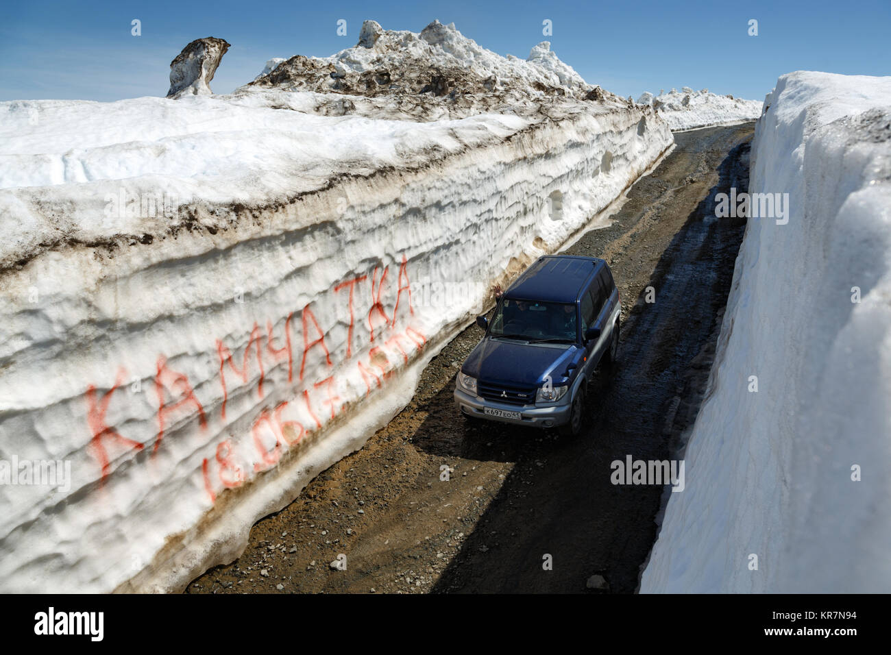 Kamchatka Peninsula, Russia: Japanese off-road car Mitsubishi driving on mountain road in snow tunnel surrounded - Stock Image