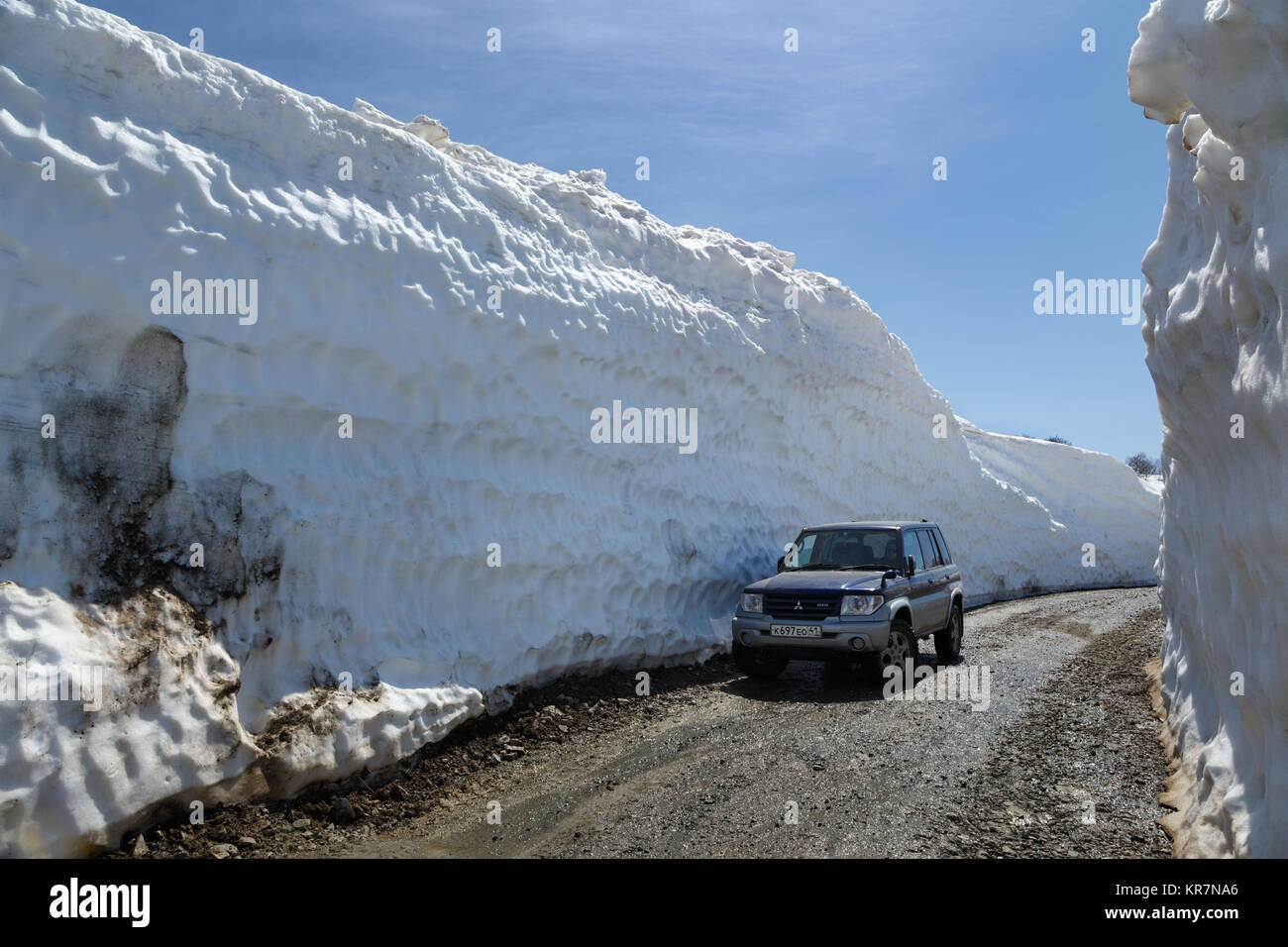 Vilyuchinsky Volcano, Kamchatka Peninsula: Japanese off-road car on mountain road in snow tunnel surrounded by high - Stock Image