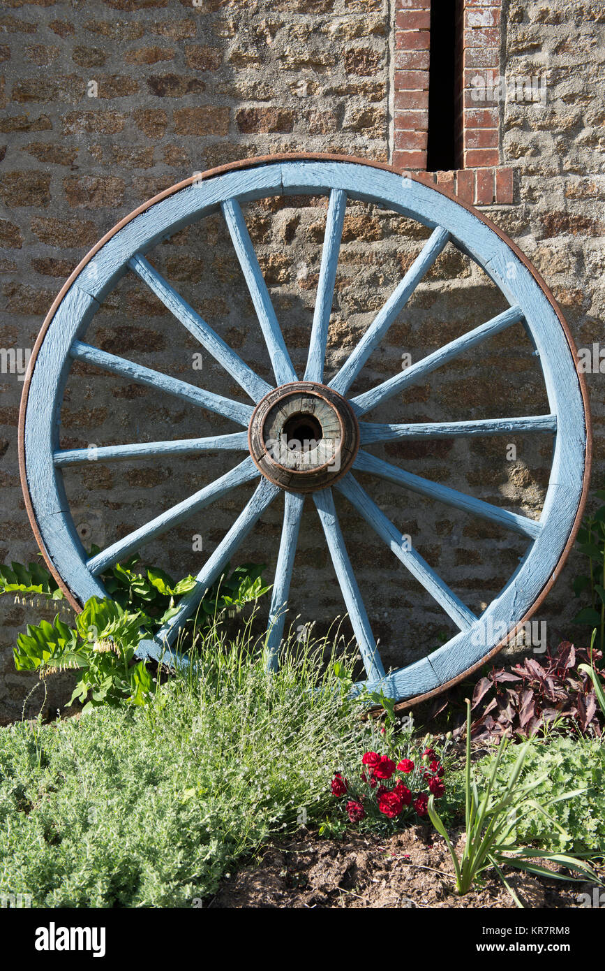 An old cartwheel leaning against a barn wall in Mayenne, France. - Stock Image