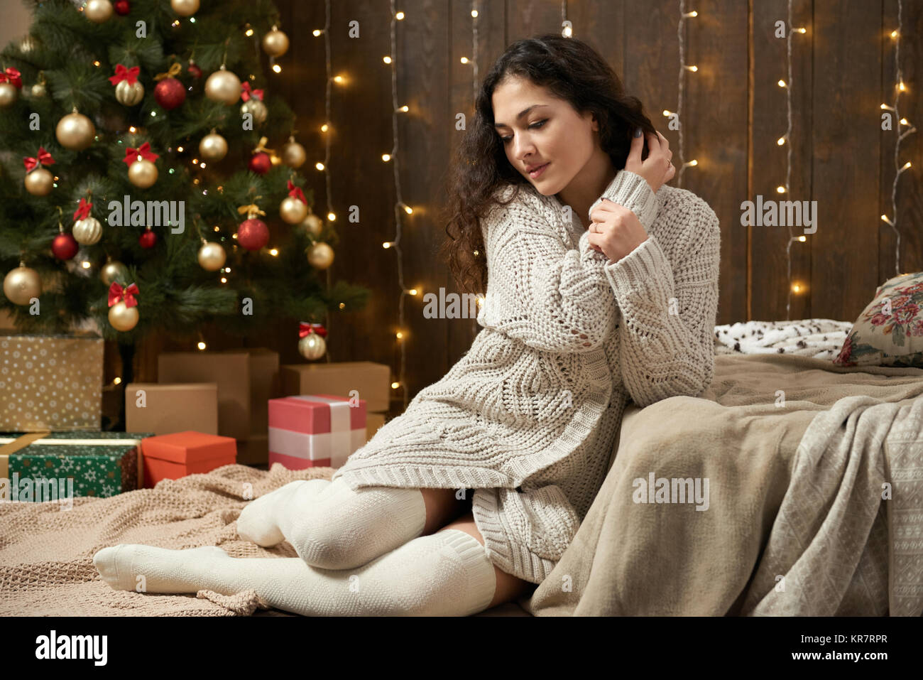 young girl in christmas lights and decoration dressed in white