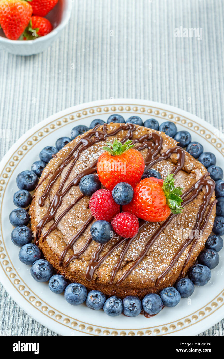 Big chocolate cheesecake with blueberry strawberry raspberry on a round plate. - Stock Image