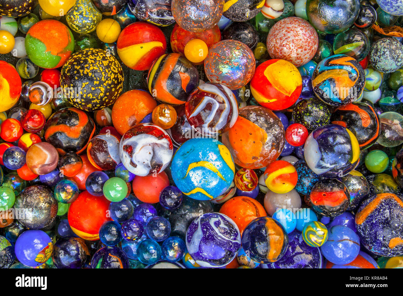 Glass marbles of different sizes in a color pattern as methaphor for multicultural community diversity - Stock Image