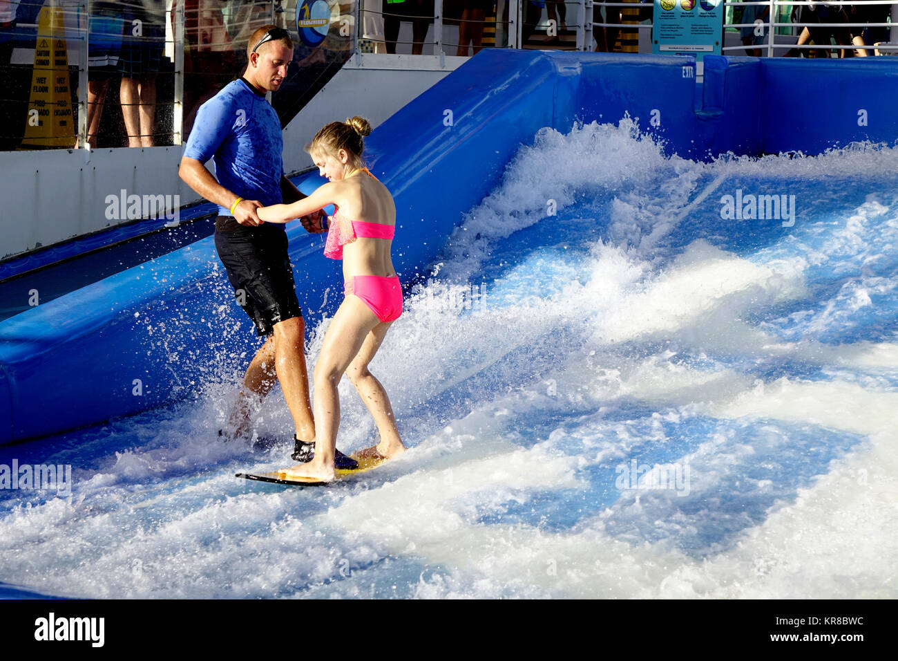 An attendant on the Liberty of the Seas Flowrider helps a young passenger into the flowing water before letting - Stock Image