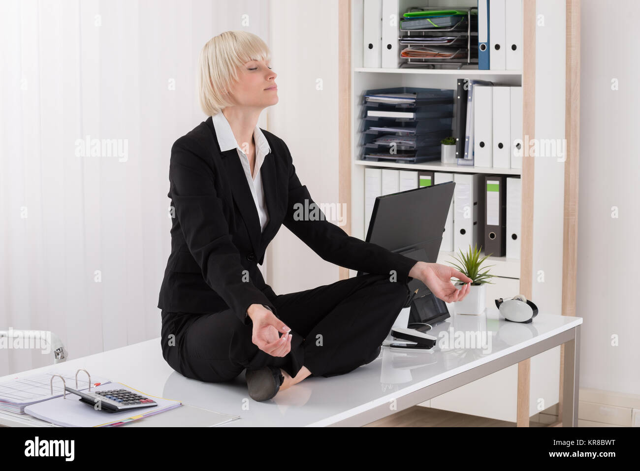 Businesswoman Doing Yoga In Office - Stock Image