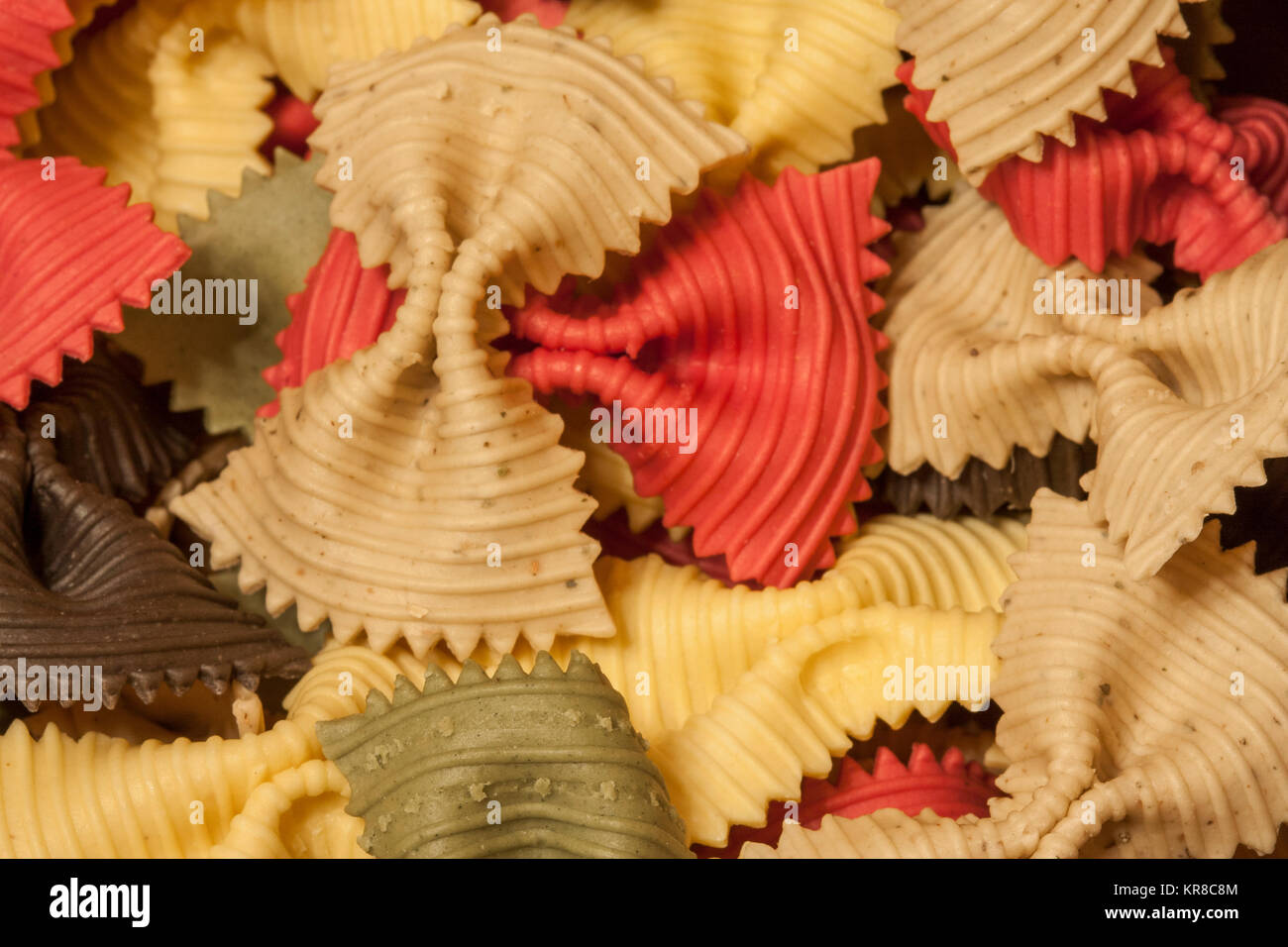 background of multicolored macaroni figured as bow Stock Photo