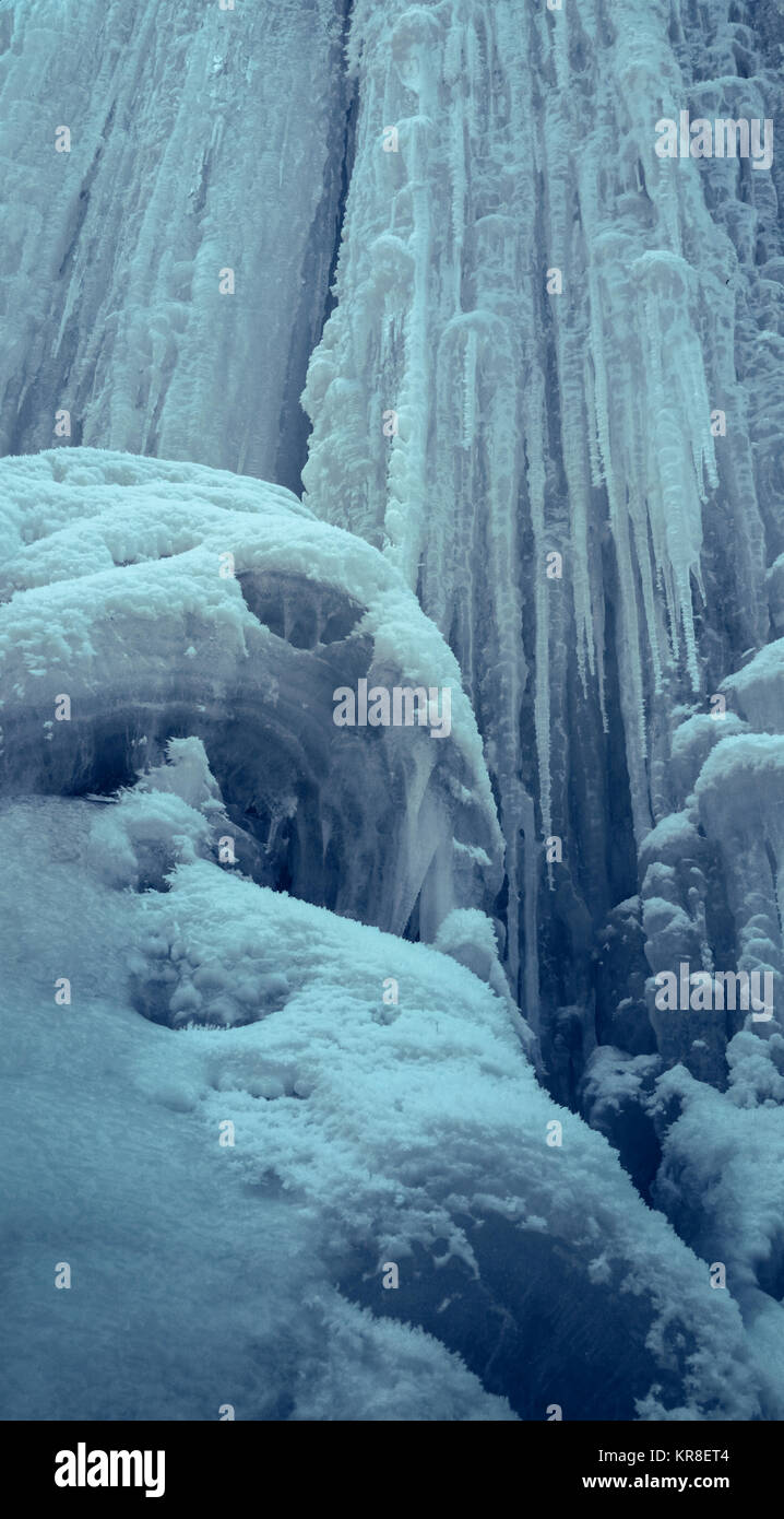 Vertical steep ice wall with long icicles. Frozen waterfall. - Stock Image