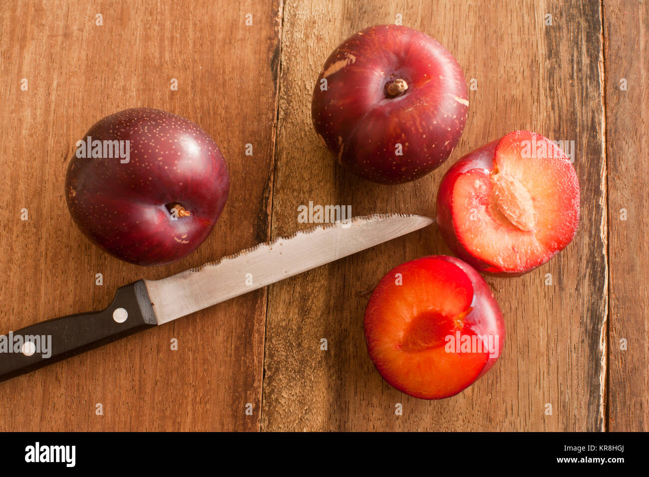 Organic Plums and Sharp Knife on Wooden Table Stock Photo