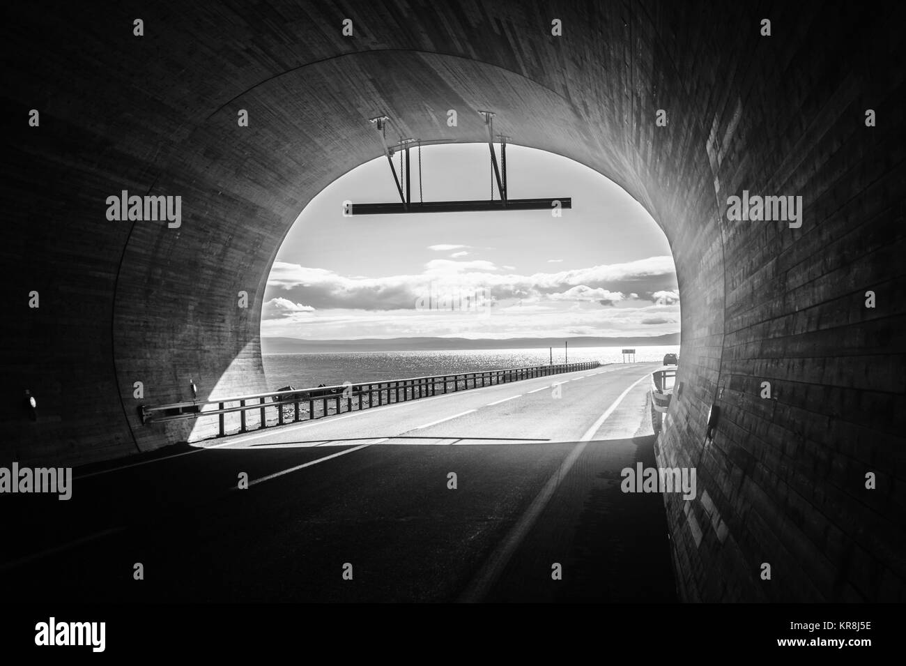 View from the tunnel to the blue cloudy sky and sea, Finnmark, Norway - Stock Image