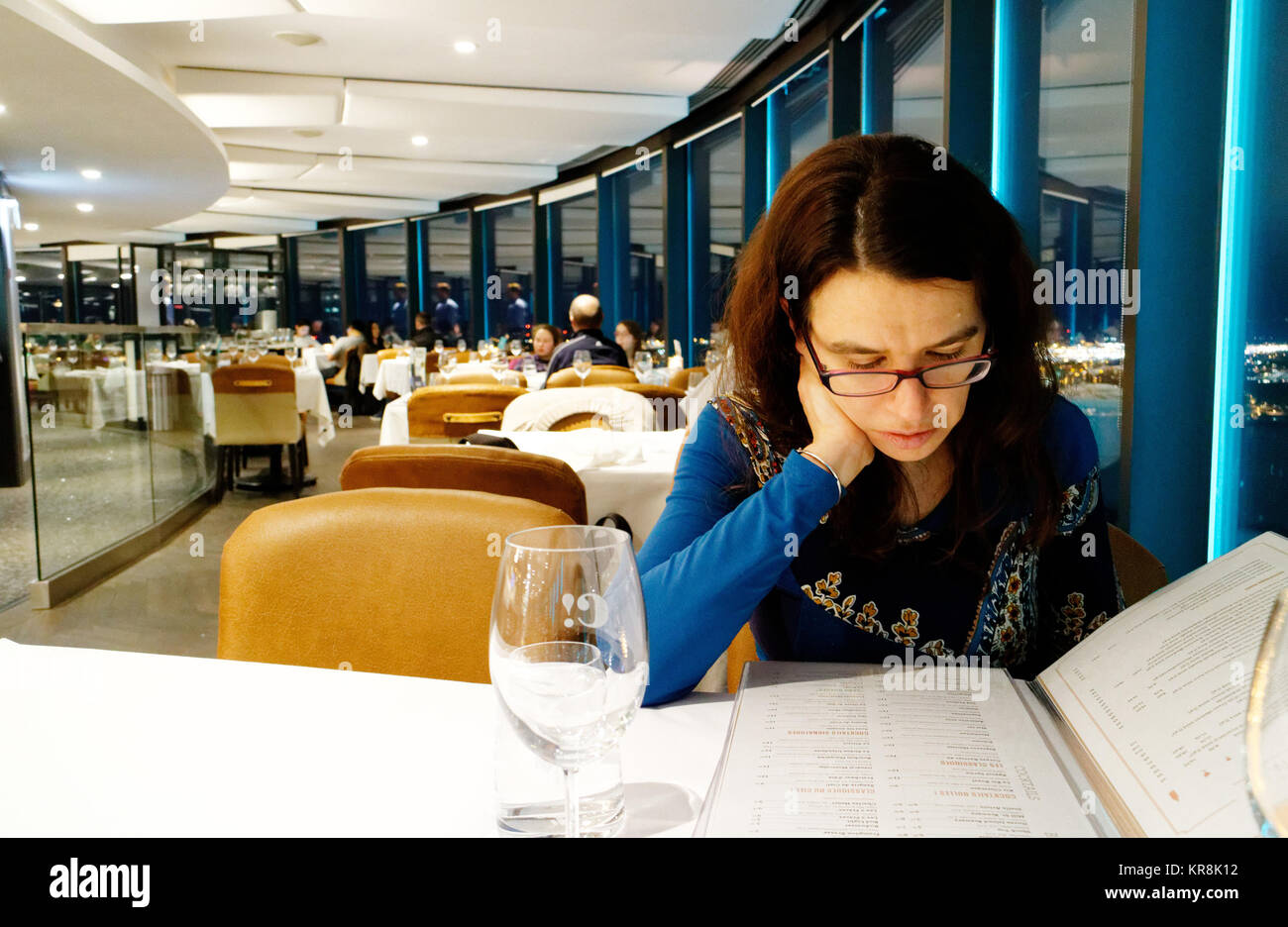 A lady diner looking at the menu is the Ciel! rotating restaurant in Qiebec City - Stock Image