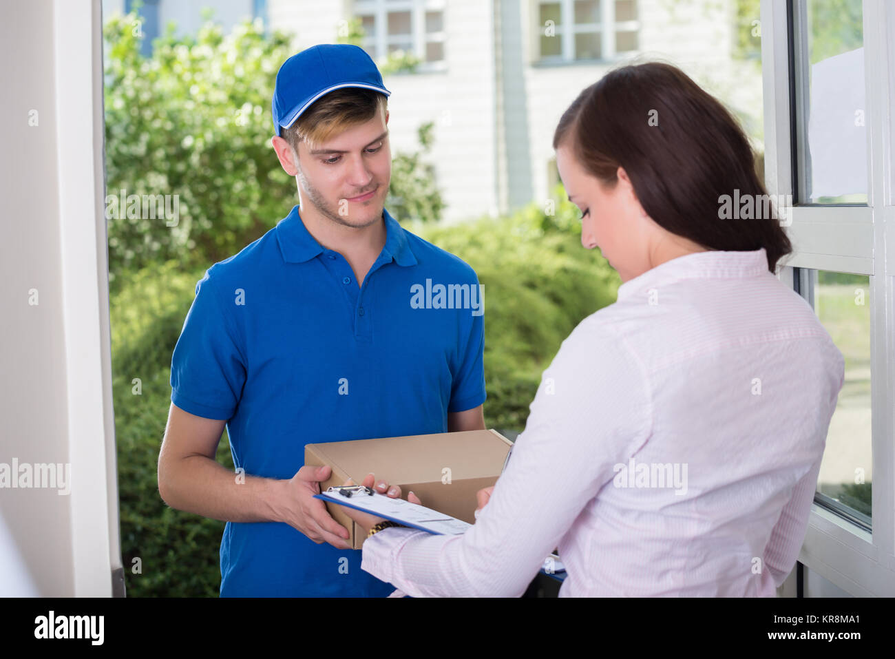 Woman Signing Receipt Of Delivery Package - Stock Image