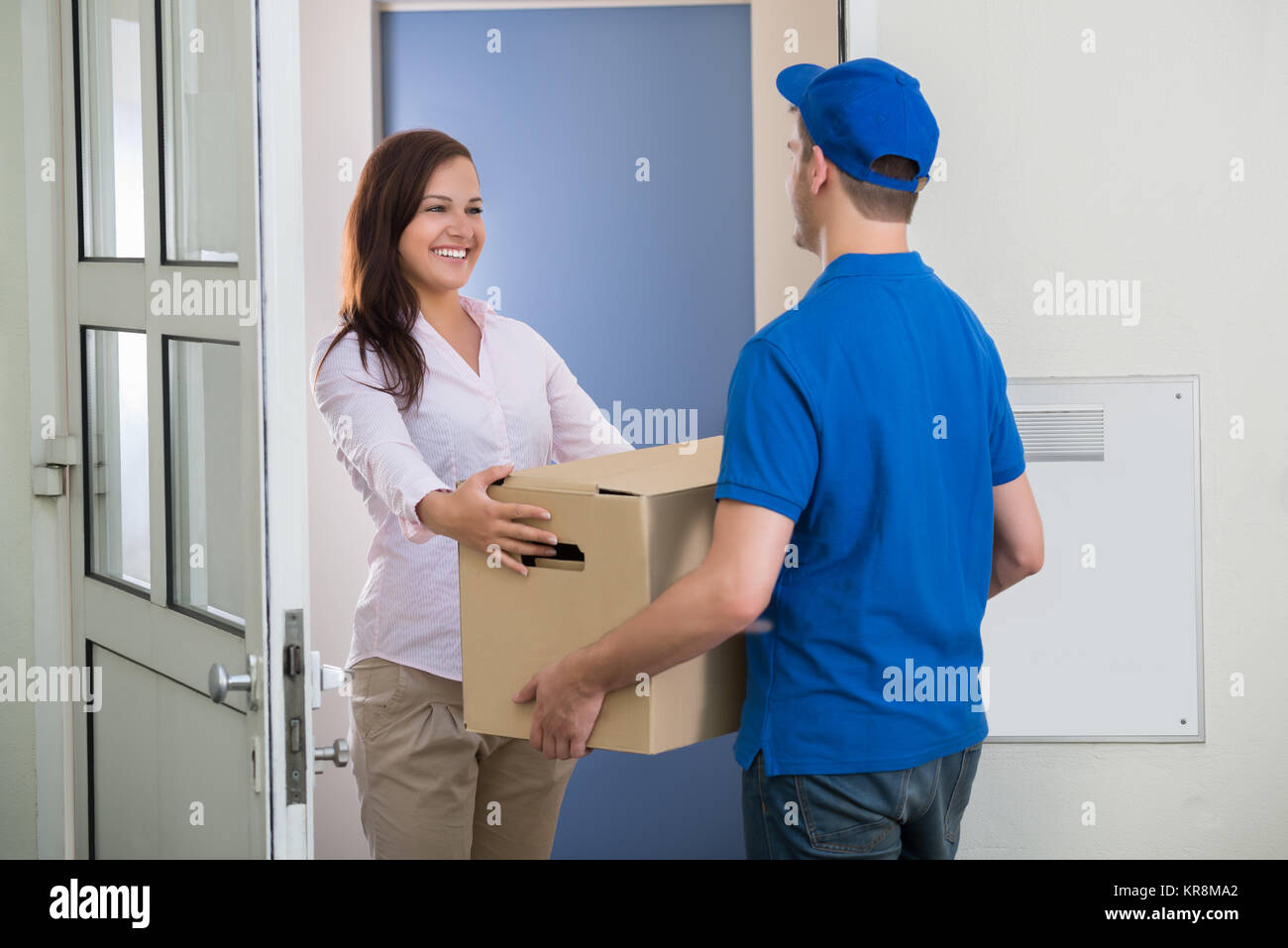 Delivery Man Gives Package To Woman - Stock Image