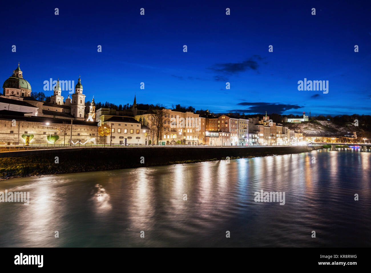 Austria, Salzburg, Riverbank with buildings at night - Stock Image