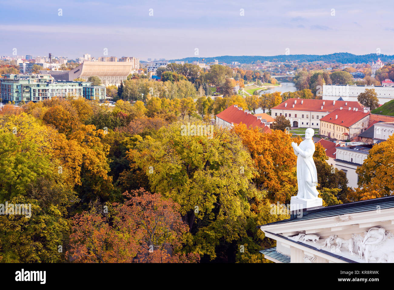 Lithuania, Vilnius, Statue on roof with cityscape in background - Stock Image