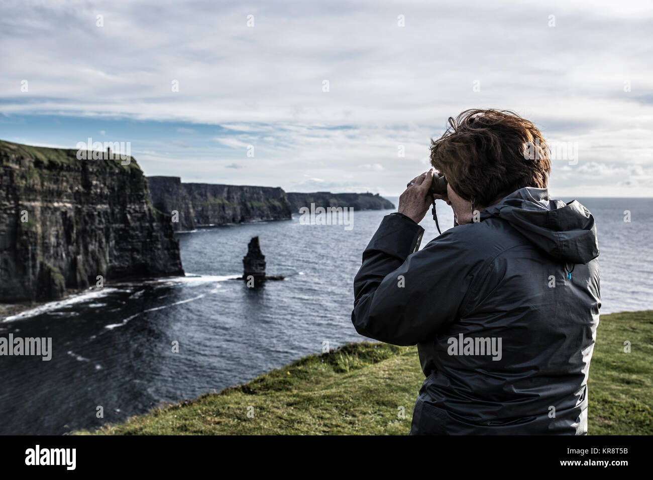 Ireland, Clare County, Woman looking through binoculars on Cliffs of Moher - Stock Image