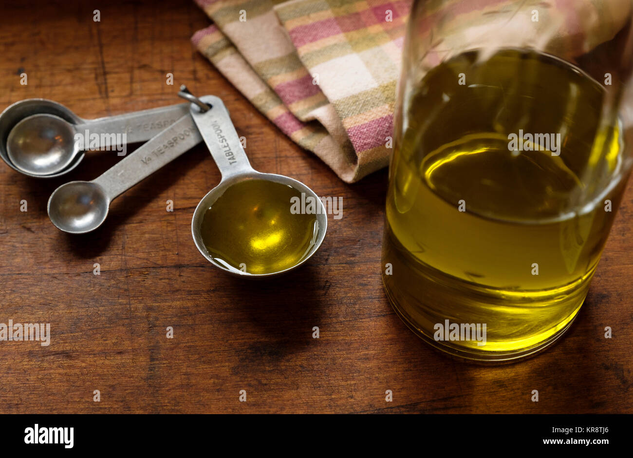 Measuring spoon, olive oil and napkin - Stock Image