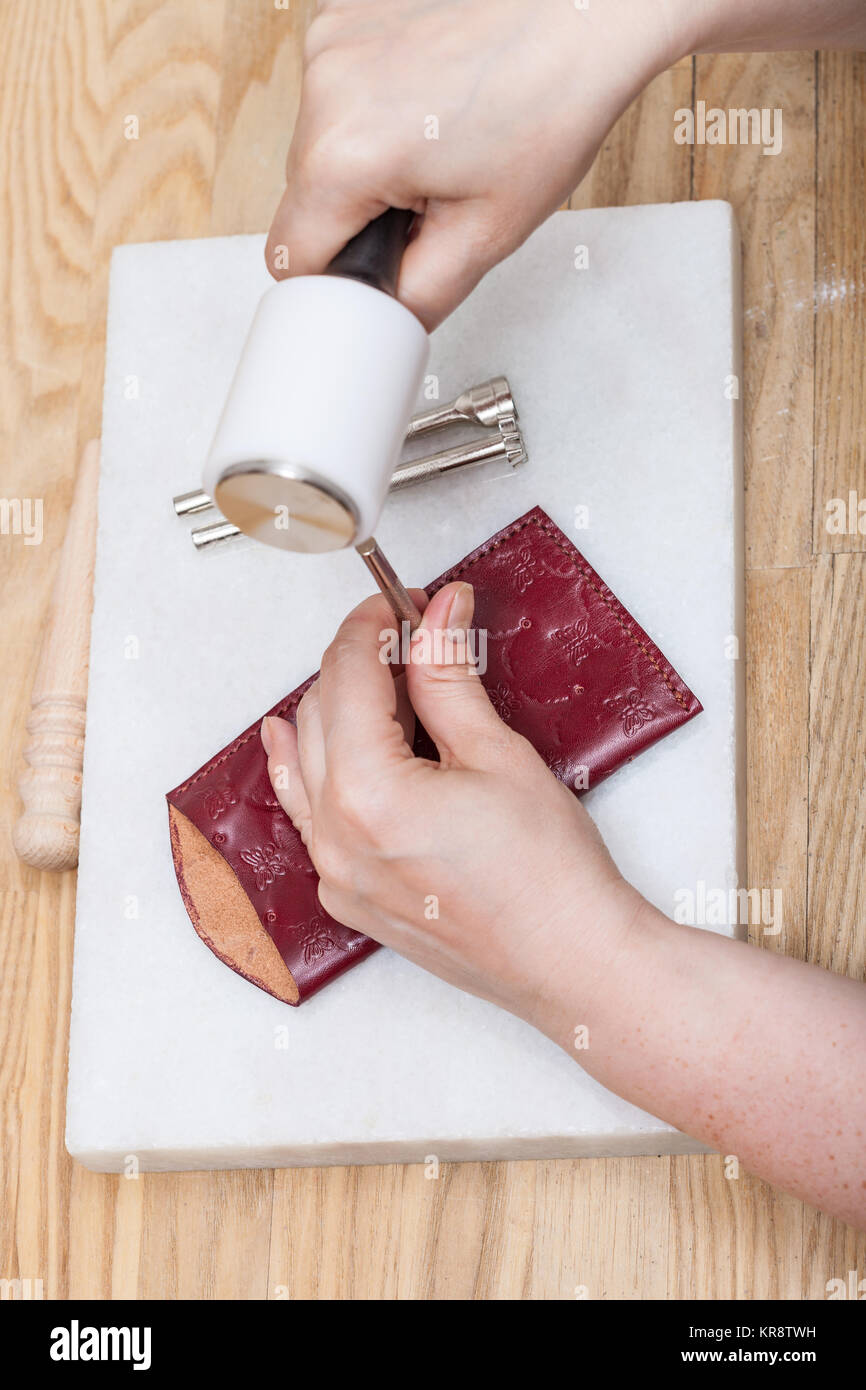 craftsman corrects stamping of leather pouch - Stock Image
