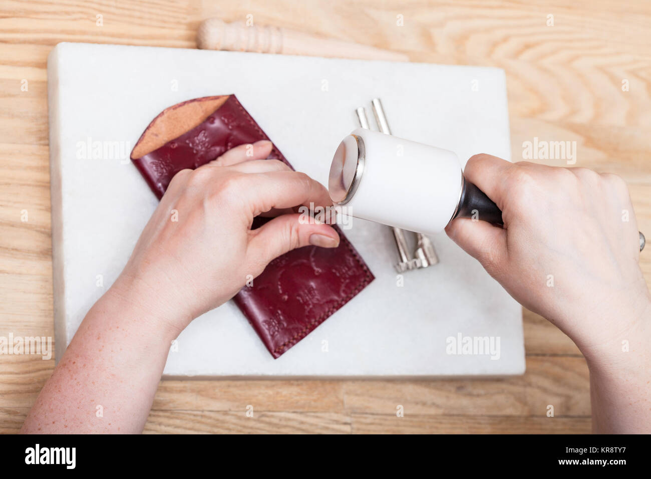 craftsman corrects embossing of leather pouch - Stock Image