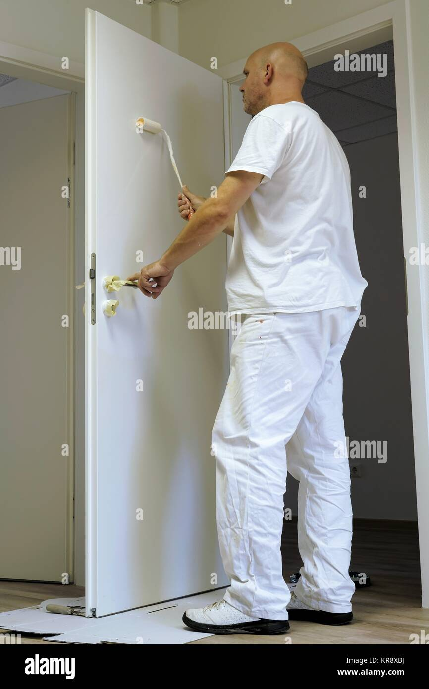 craftsmen in the paint a door in an office building - Stock Image