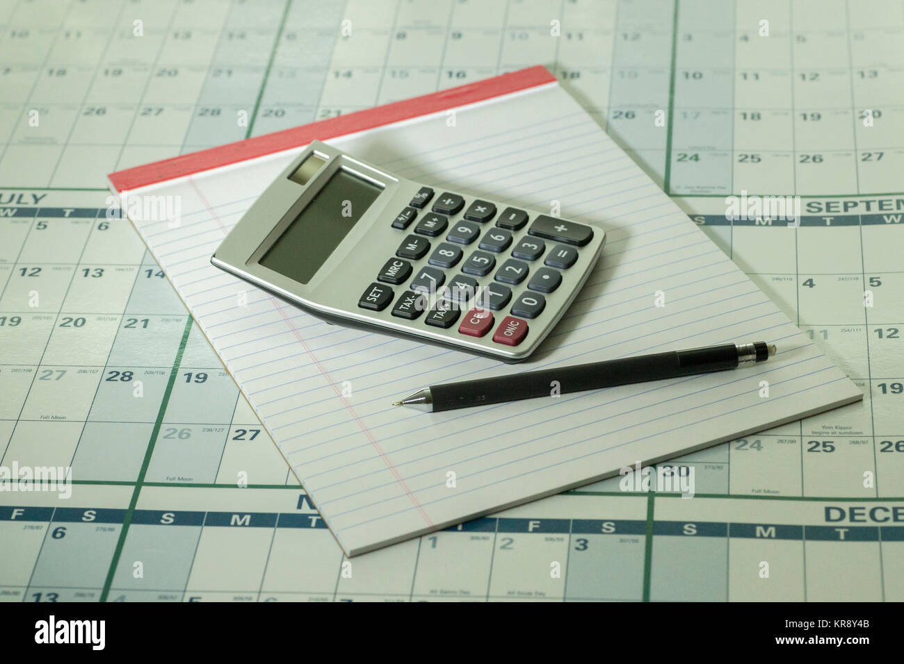 Calculator pad and pencil  on calandar background - Stock Image