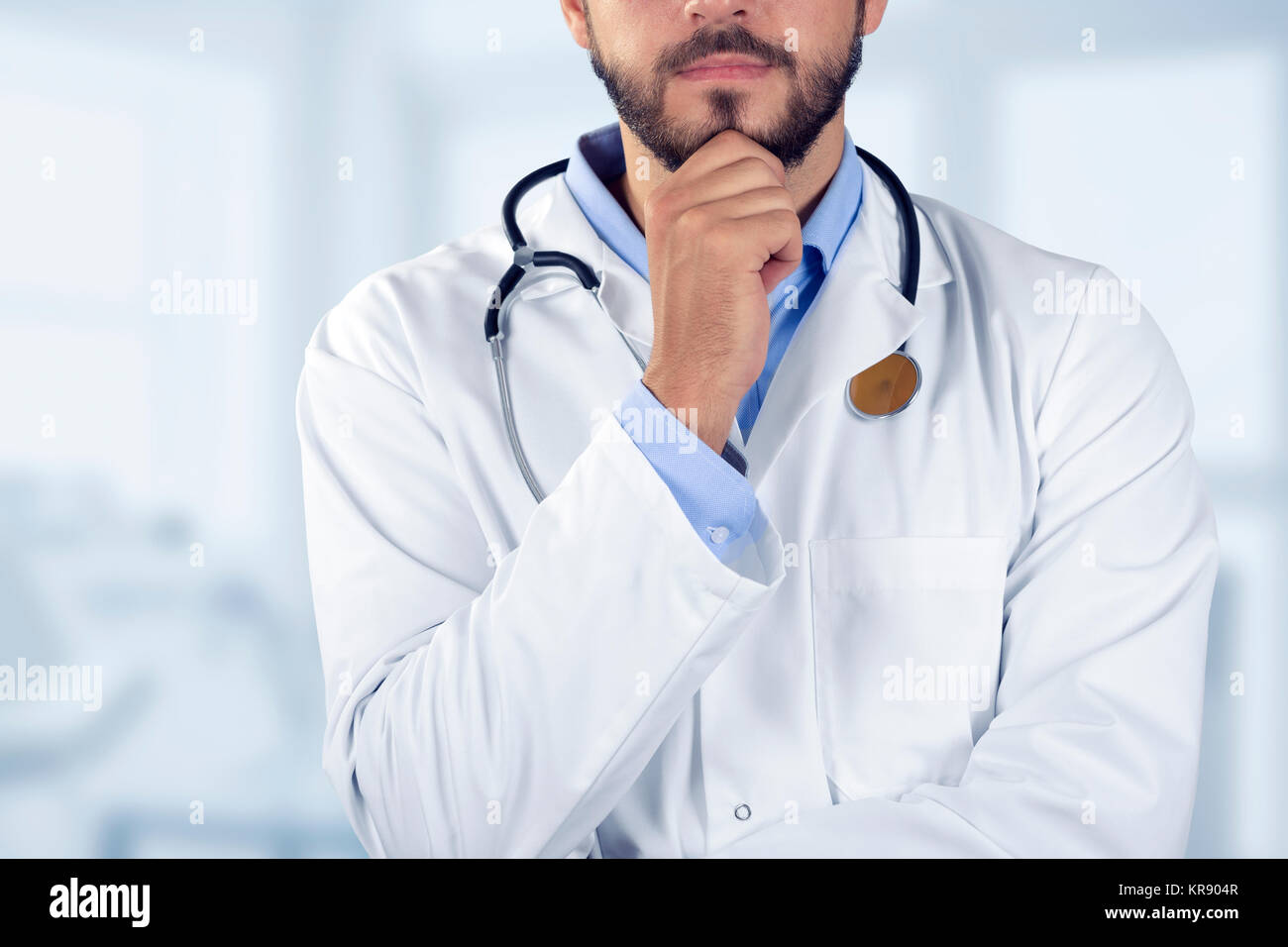 doctor standing with hand on chin - Stock Image