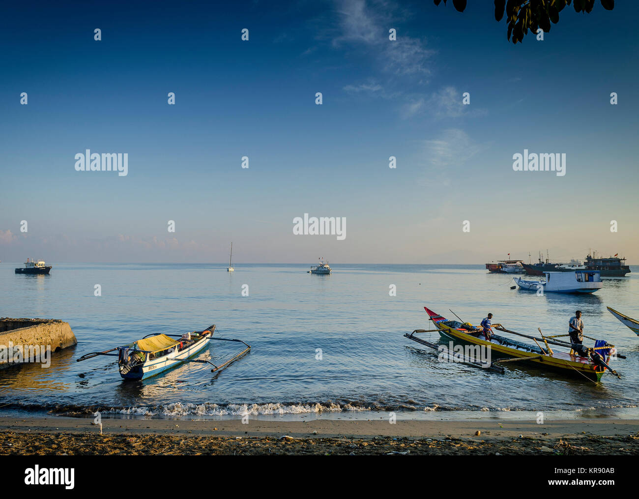 coast with traditional fishing boats on dili beach in east timor leste - Stock Image