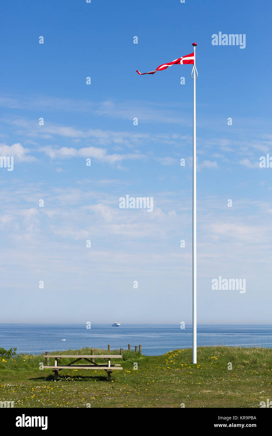 danish flag in the wind against a blue sky - Stock Image