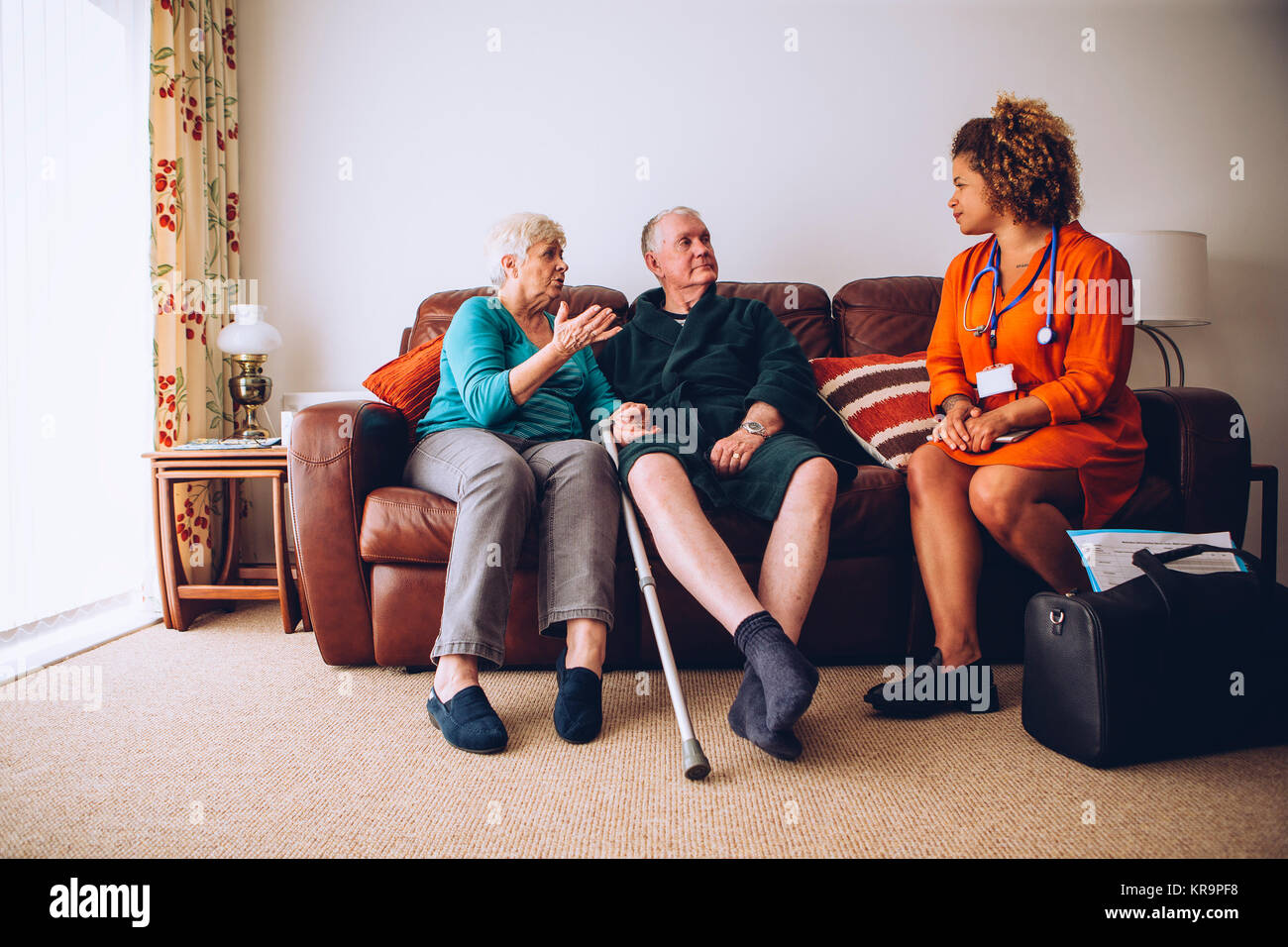 Elderly Couple with Home Carer Stock Photo