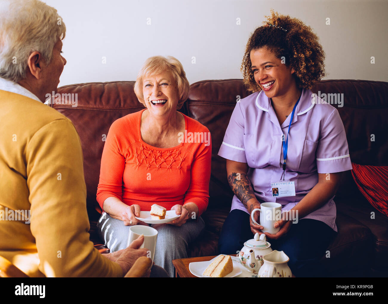 Caregiver Sharing Tea Time with her Patients - Stock Image
