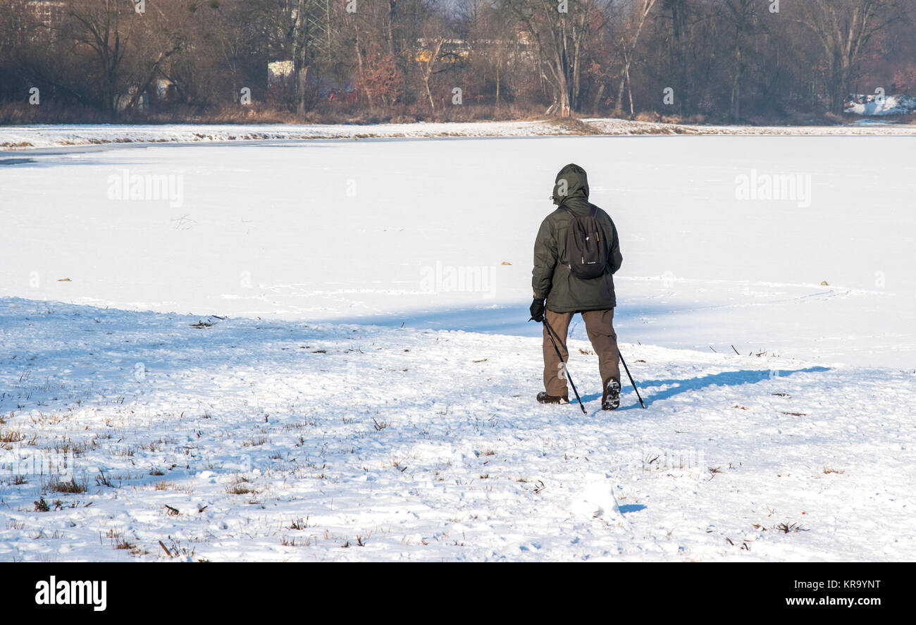 men with trekking poles on a lonely winter expedition photo - Stock Image