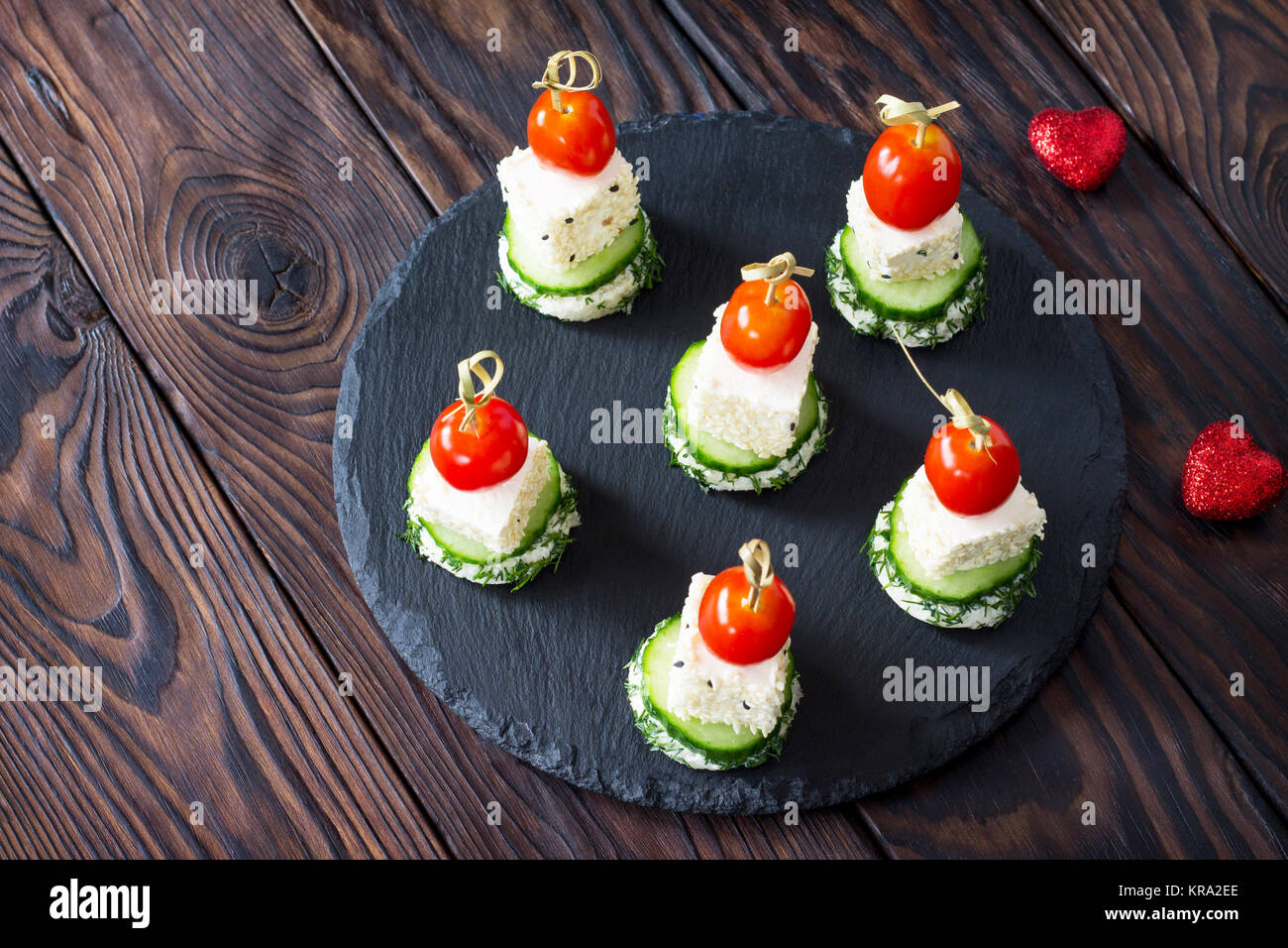 Appetizer canape with white bread, feta cheese, cucumber and cherry tomatoes on a wooden table. - Stock Image