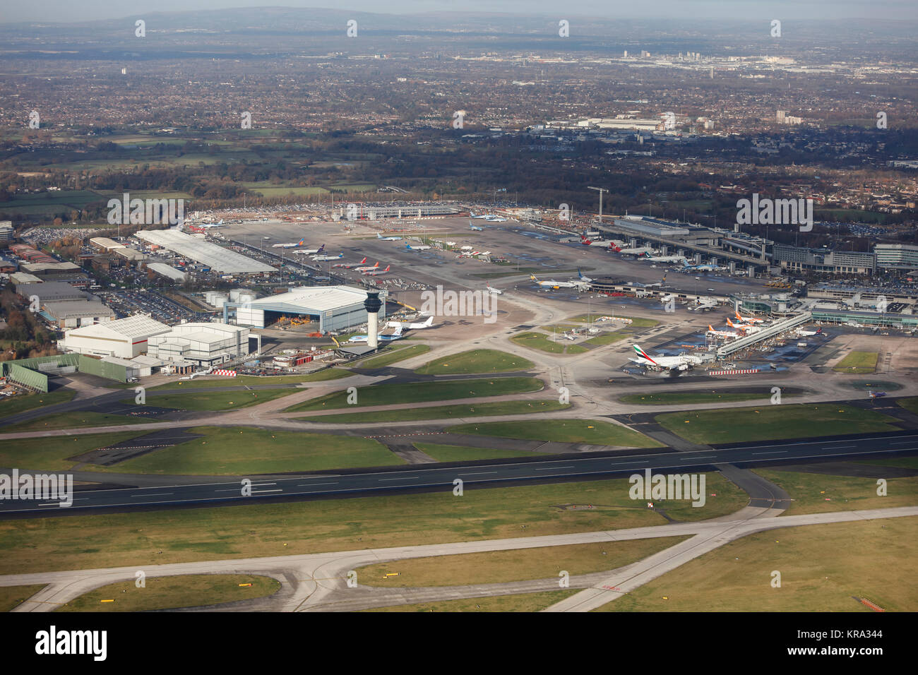 An aerial view showing hangars, the control tower, aprons and terminals of Manchester Airport. - Stock Image
