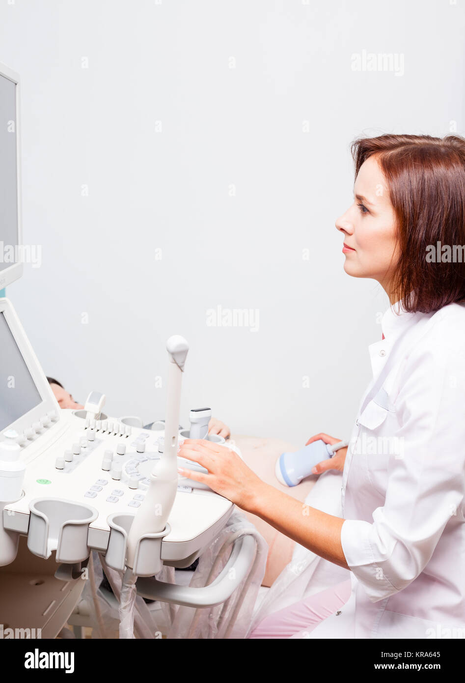 Sonographer scanning young pregnant woman's belly with ultrasonic transducer doing obstetric ultrasonography - Stock Image