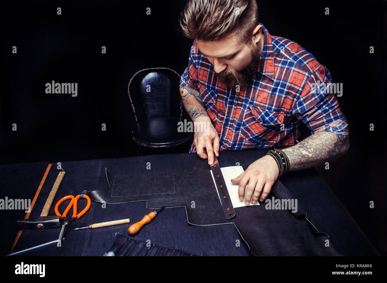 Leather Currier creating new leatherwork in the work area./Currier of leather processes a workpiece from leather - Stock Image