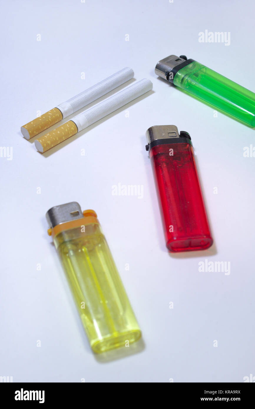 Multicolored disposable flint gas lighters and filter cigarettes - Stock Image