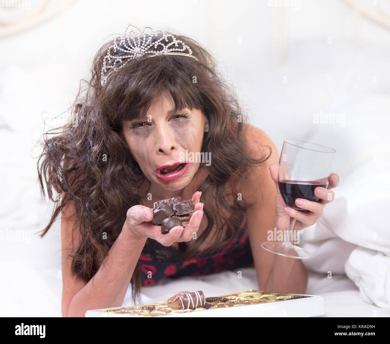 Sobbing Woman in Tiara Drinking Wine and Cramming Chocolates in Bedroom - Stock Image