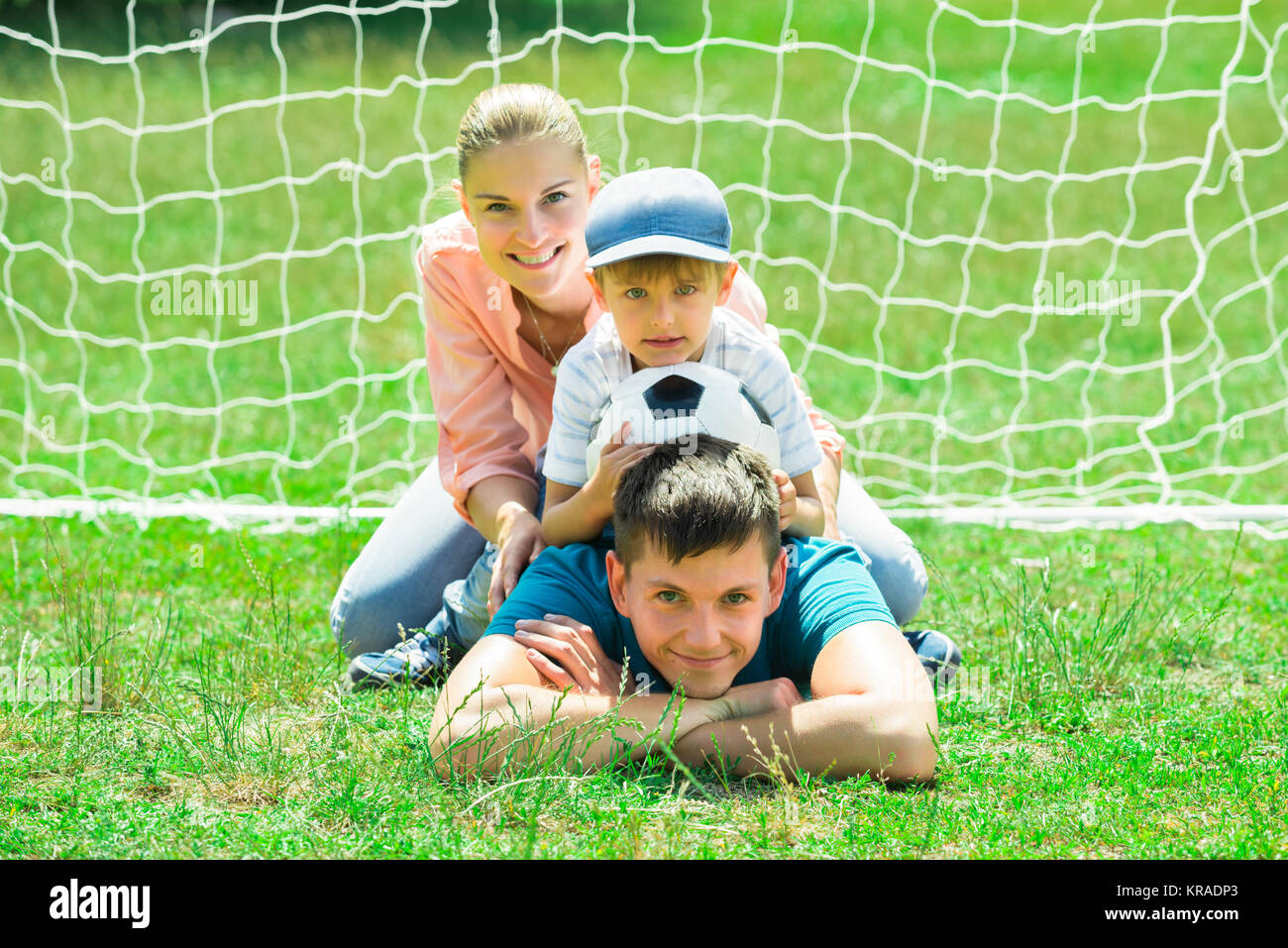 Portrait Of Happy Family With Soccer Ball - Stock Image