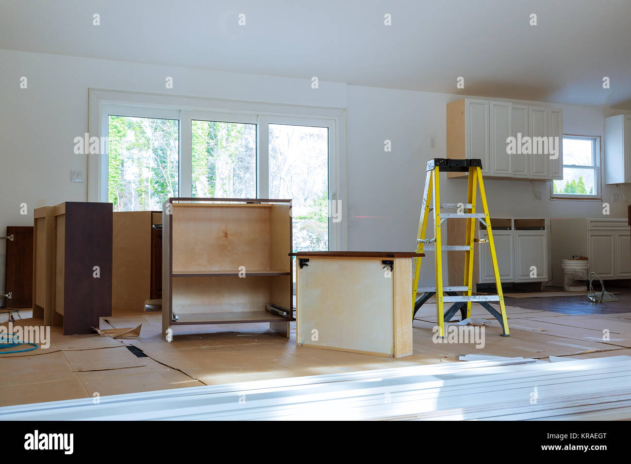 Installing new induction hob in modern kitchen Installation of kitchen cabinet. Stock Photo