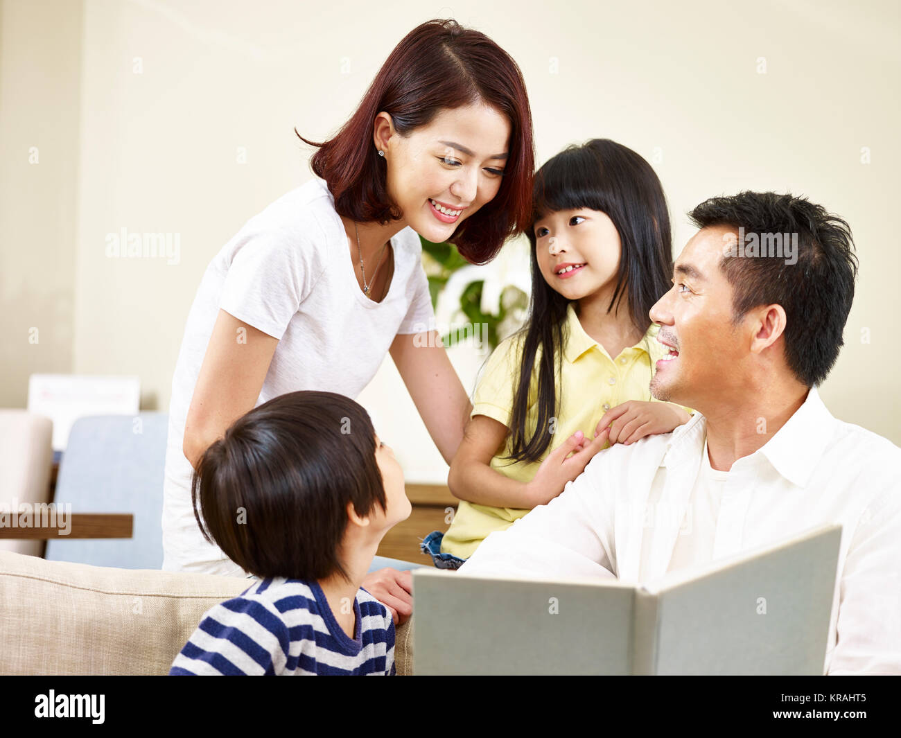 asian parents mother and father and two children son and daughter reading a book telling a story together. - Stock Image